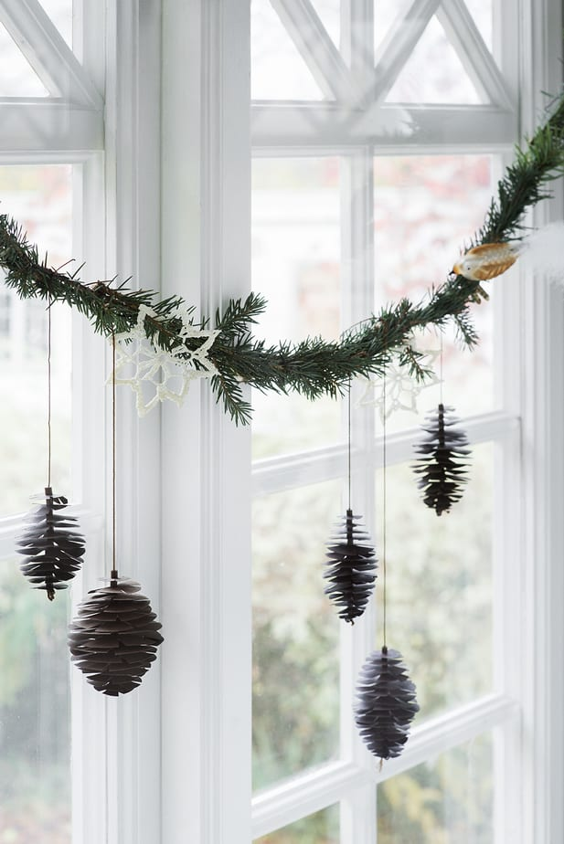 garland christmas window decor idea with pine cones paper ornaments